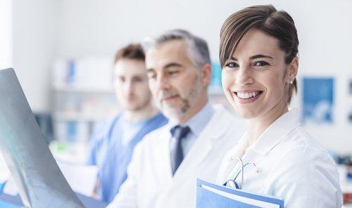 3 Ärzte stehen zusammen, wobei die Frau in die Kamera lächelt