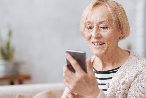 Frau benutzt Ihr Smartphone zur Bedienung einer EGK-App.