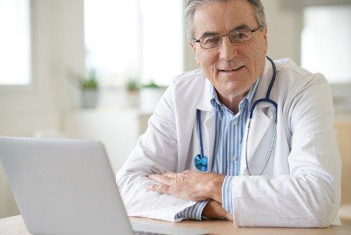 Älterer Arzt sitzt am Praxistisch