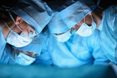 Vier Ärzte stehen über einem Patienten und operieren.