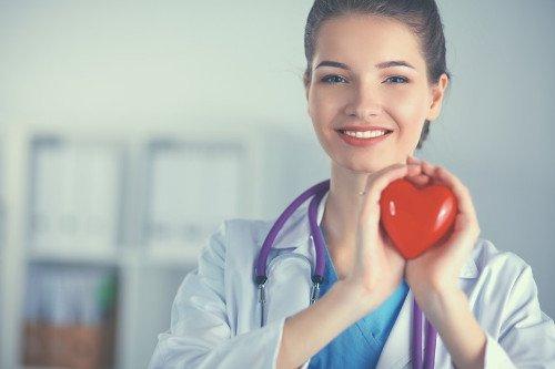 Ärztin hält rotes Herz in Händen und lächelt.