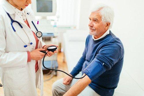 Ärztin misst bei älteren Herrn den Blutdruck.
