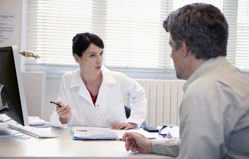 Ärztin redet mit Patient und hält dabei einen Stift in der rechten Hand.