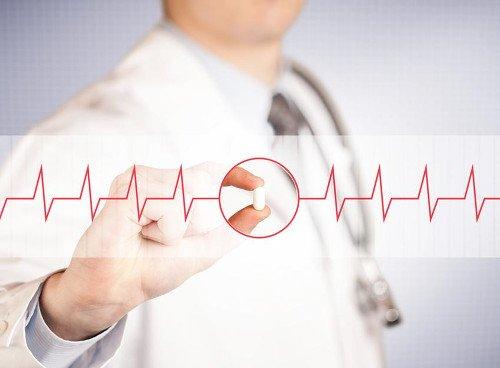 Arzt hält Kapsel zwischen Zeigefinger und Mittelfinger. Daneben gehen EKG-Auschläge nach außen weg.