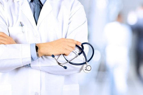 Arzt mit Stethoskop und verschränkten Armen.