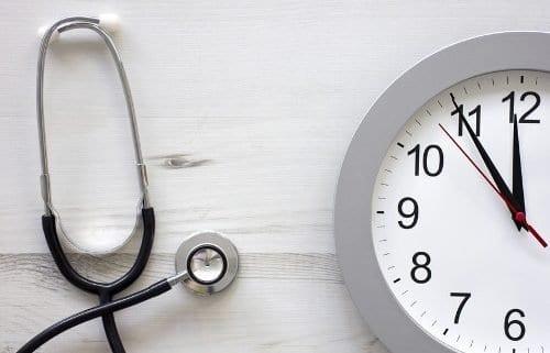 Stethoskop liegt neben einer Uhr.